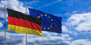 Germany and European Union waving flags on blue sky background